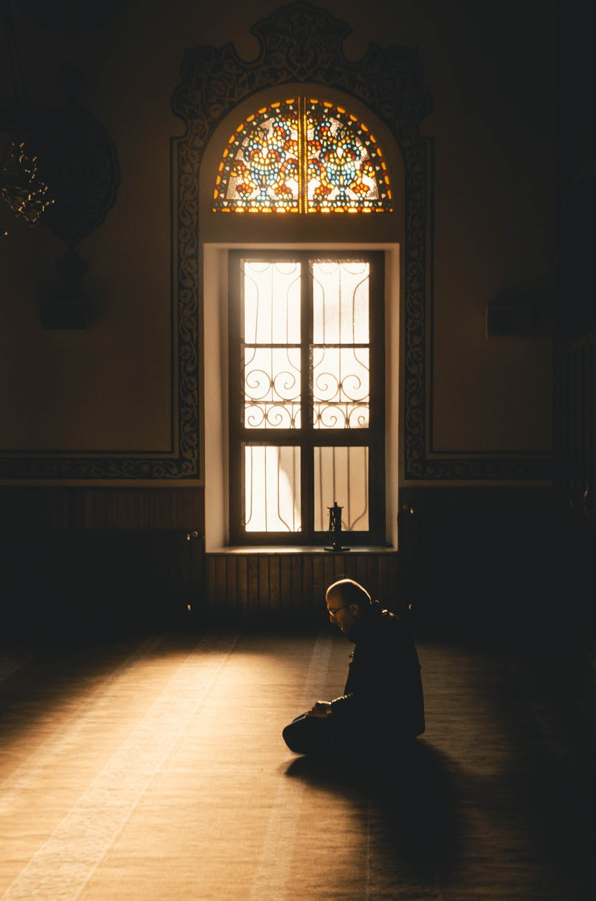 Man sitting on the floor in a dark church, with only a window at the side of him giving in light.